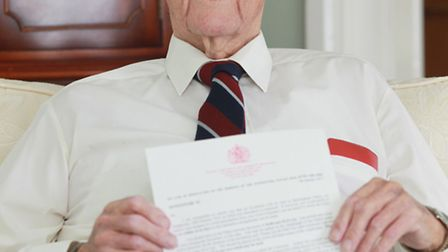 John Stoddard at home with his letter for his MBE for services to Letchworth