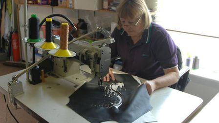 Catherine Woodley works on one of the designs from the film
