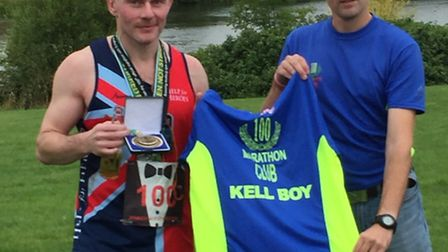 Richard Kell receiving his 100-club vest from Enigma Running race director David Bayley.