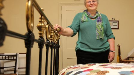 Barbara Millman, Project Leader with the replica Victorian Quilt which was handmade by volunteers