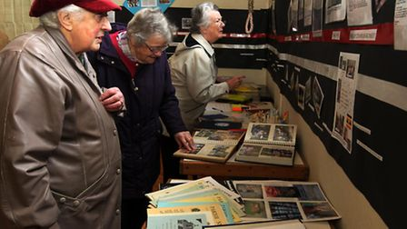 Visitors look at the centenary display in the church.