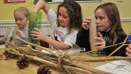 Girls attending a fire safety day and a hedgehog rescue event have a go at making an insect hotel