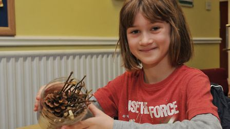 A girl attending a fire safety day and a hedgehog rescue event with her insect hotel