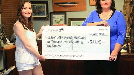 Katie Strong from Stevenage hands over a cheque to the Clearwater Marine Aquarium in Florida after r