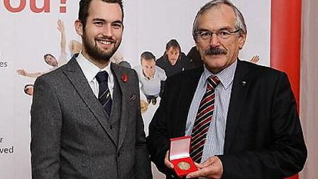 Francis Tomlinson with his medal and his son Samuel.