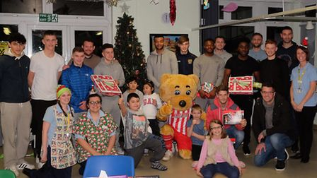 Boro bear and Stevenage FC first team and youth players hand out Christmas presents on the children'