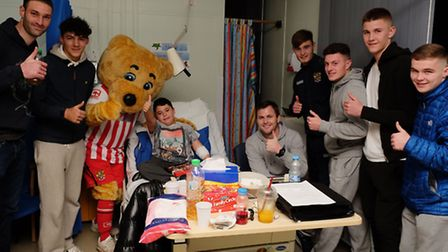 Boro bear and Stevenage FC first team and youth players hand out presents and meet Neeko Heath, 9 on
