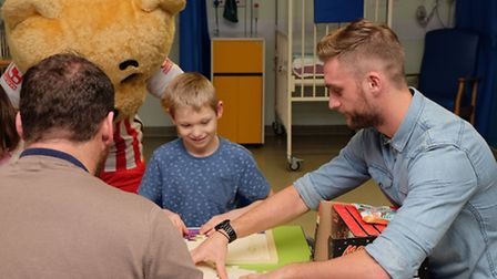 Boro bear and Stevenage FC first team player Fraser Franks play with children on the children's ward