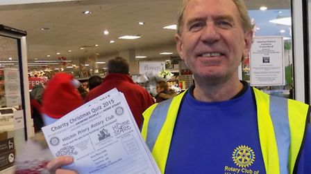 Martin Gascoigne of Hitchin Priory Rotary Club sells copies of the charity Christmas quiz to custome