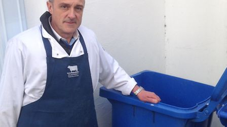 Chris Wright, from Humphreys Butchers, with the blue wheelie bin that was stolen - and then returned