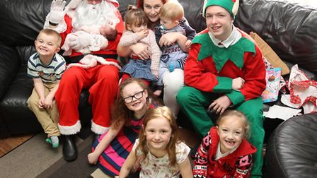 Darren Woods and son TJ dressed as Santa and elf with the Eaton family during one of their many fami