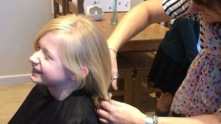 Holly Smith, 8, having her long blonde hair cut by hairdresser Kelly Degaute.