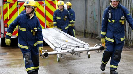 Firefighters getting ladders off fire engine
