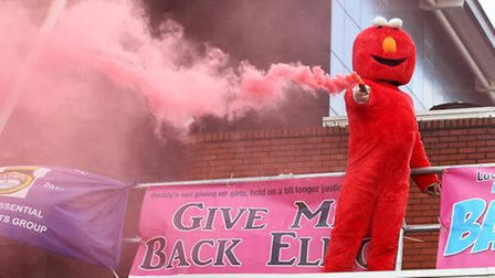Bobby Smith protests on the roof of Stevenage Police Station with a smoke flare.