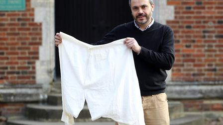 Peter Mason holds Queen Victoria's bloomers which are being put up for auction in Woburn by a woman