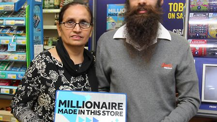 Mum Kulwinder Kaur Rehal with son Gurpreet Singh showing off the lucky shop poster they have on disp