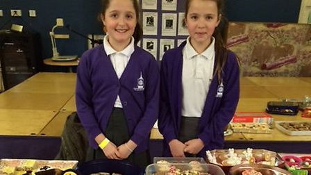 Anne's daughter Eleanor Street and Charlotte Yousif as the Wilshere-Dacre Junior Academy cake sale