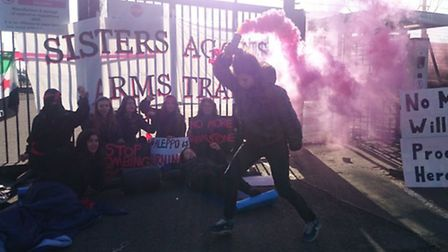 An activist lets off a flare during the Sisters Against Arms Trade protest outside MBDA's Henlow sit