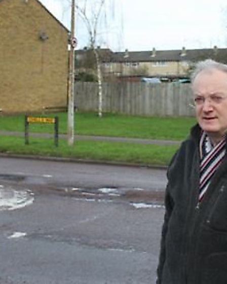 Stevenage councillor Robin Parker in Chells Way, which was littered with potholes.