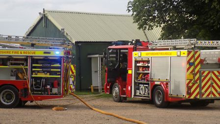 Firemen at the scene of a fire which destroyed a building at Hitchin Cricket Club's Lucas Lane groun