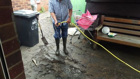 Tony and Pat Page cleaning up the sewage after it overflowed through the toilets and kitchen drains
