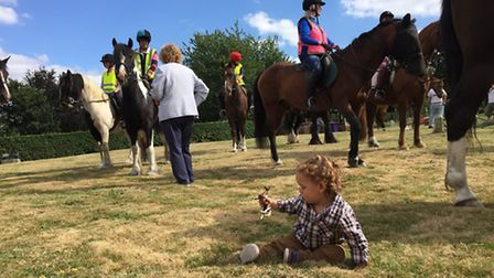 Thomas Asher, one, plays with a toy horse during the horse blessing service at St Ippolyts Church on