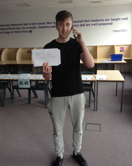 Marriotts School's Charlie Braxton with his A-level results as he makes a call to pass on the good n