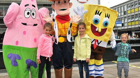 Maddie, six, Megan, six, and Ella Mead, three, with cartoon characters at the Woody's Wild West even