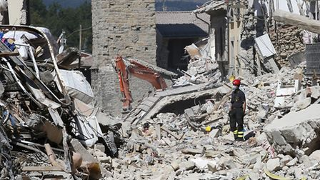 Firefighters clear rubble in Amatrice, Italy, on Monday, four days after the earthquake hit. Photo: