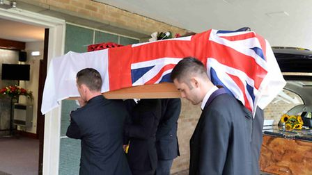 George McDowell's coffin is carried into the crematorium. Photo: Dick Goodwin