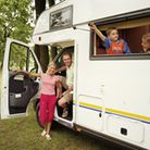 Parents and children (8-11) in motorhome, smiling, portrait of parents
