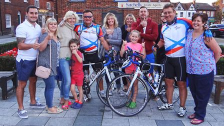 Dave Sharp and Garry Tucker with family and friends at the end of their cycle ride from Baldock and