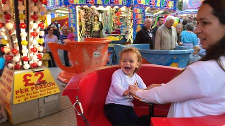 Two-year-old Thomas Asher enjoys a ride on the tea-cups with his mother Dalia.