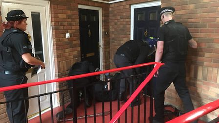 Police break down a door at Roundmead, Stevenage, this morning.