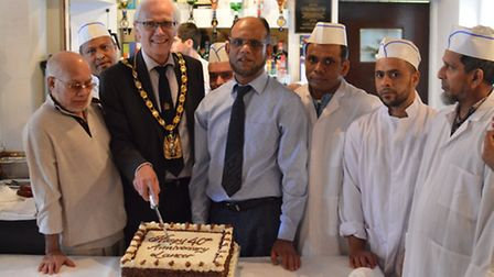 North Herts District Council chairman Councillor John Booth cuts the cake, flanked by Lancer co-owne