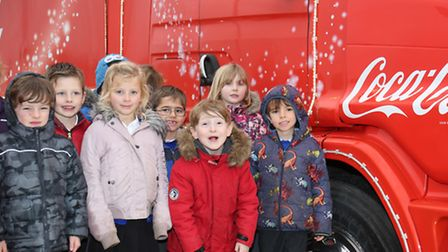 Children from St Mary's Infants year 2 pose with the Coca-Cola truck.