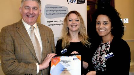 Paul Gower presents the certificate of donation to Garden House Hospice Care's Lisa Seccombe and Jor