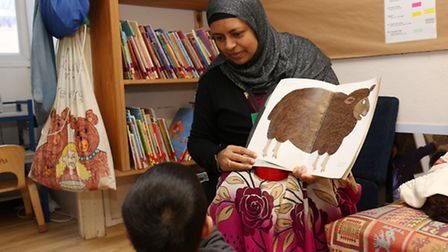 York Road Infants learning support assistant Afia Begum with a child in the library.