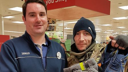 A member of Tesco staff donating trainers to Robbie
