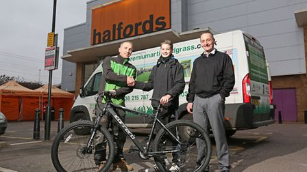 Premium Artifical Grass owner Justin Brown presents Luis, 13, and dad Jason De-Vall with a new bike