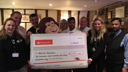 Abbas Ahmed, centre, presents the cheque to Natasha Robertson and Maria Alexander from Herts Air Amb