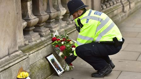 A police office leaves flowers at the scene of yesterday's London terror attack in Westminster. Pict