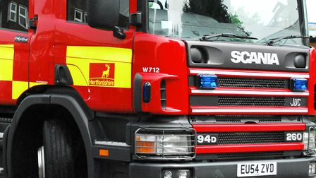 Firefighters tackled burning hedges on a road into Baldock this lunchtime after a car on fire left t