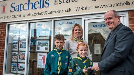 Kevin Duff, manager of Stotfold Satchells, presents a donation of 100 to Stotfold Cub Scout leader S