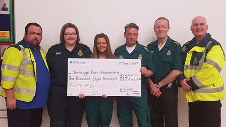 Rhiannon Fraser (third from left), along with colleagues, accepts a cheque from Roebuck Primary Scho