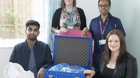 Judith Pooni and her husband Raj present the cuddle cot to bereavement officer Lou Thomas and bereav