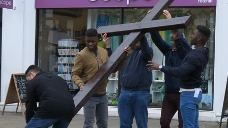 One of the crosses is raised in Hitchin's Market Place after the Walk of Witness on Good Friday. Pic