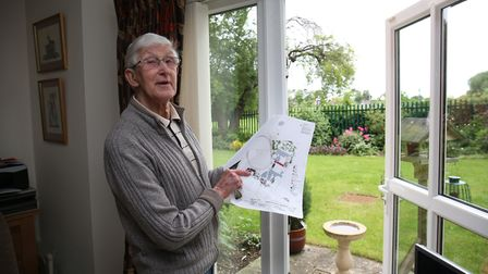 Archers Court resident John Harling in his living room points to the planned new building of Hitchin