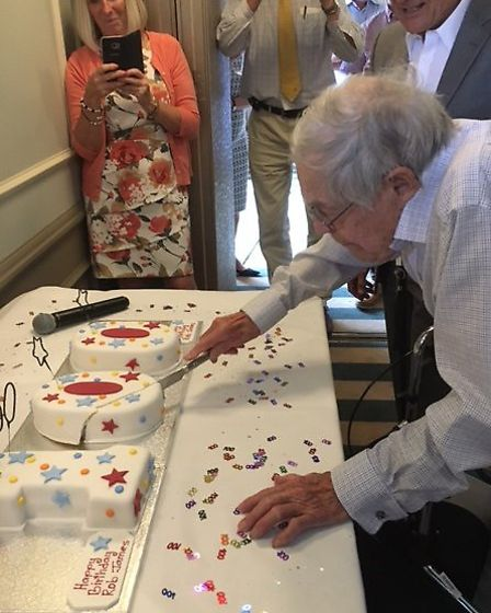 Rob James cuts his cake to mark his centenary.