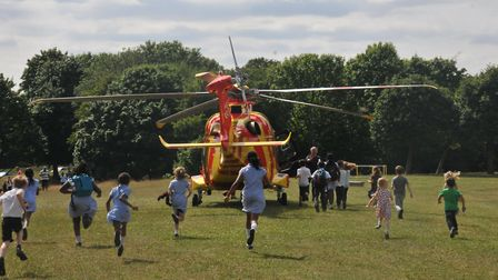 Children run towards the new Essex & Herts Air Ambulance just after its landing at Fairlands Valley